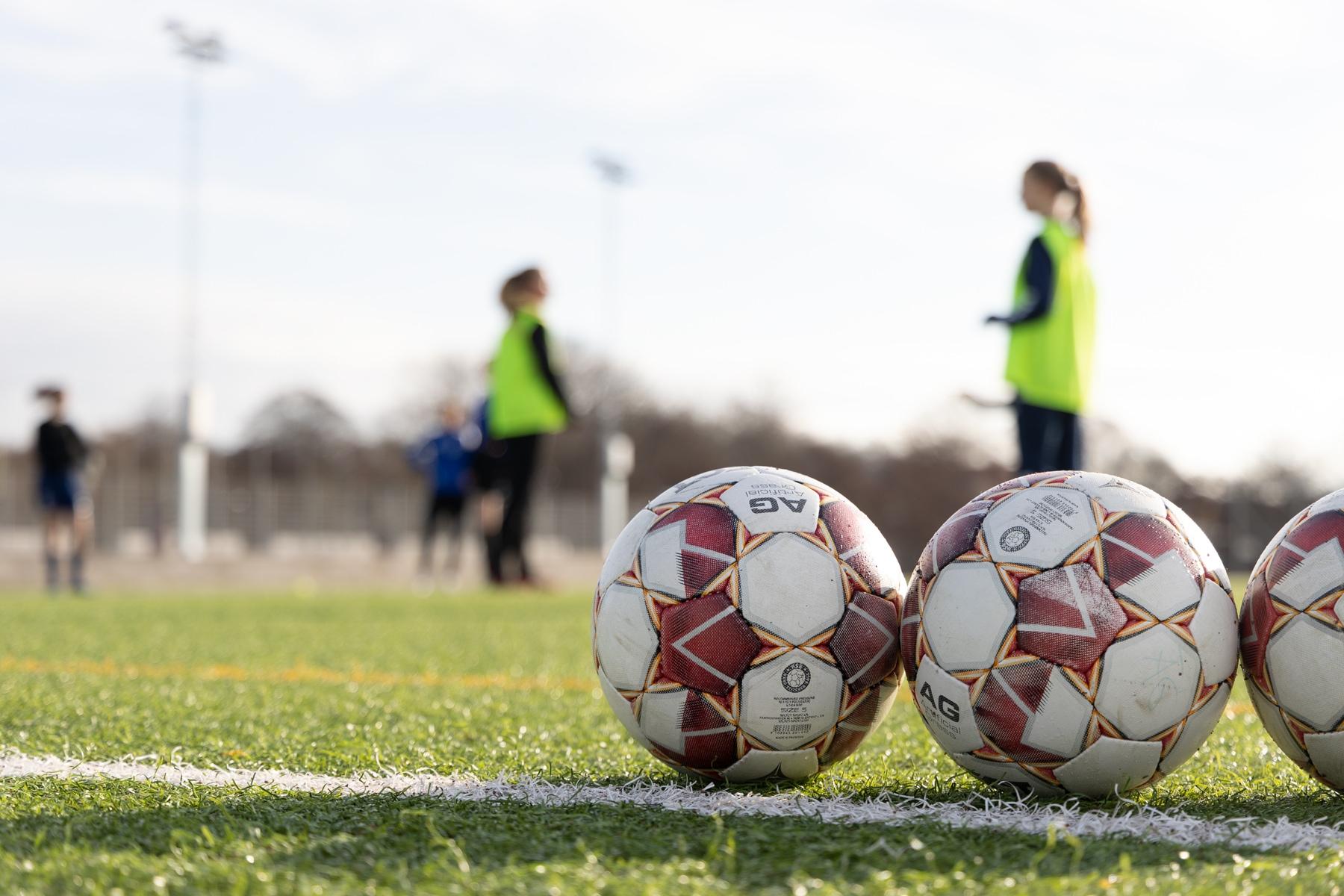 Fotbollar och fotbollsspelare under en träning på Änglagårdsskolan.